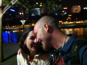 Jen and Chris embracing in Melbourne Australia, a central stop in their global travel