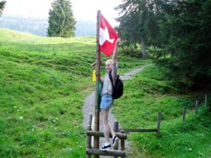 Student intern house-sitting and travelling in Switzerland poses with Swiss flag on mountain