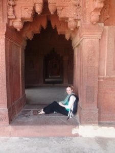 Ellie sits in the archway of a Hindu temple in India