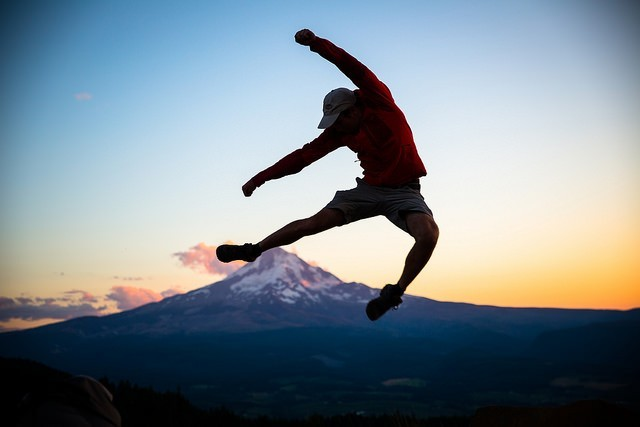 young traveler jumping for joy against a sunset mountain setting