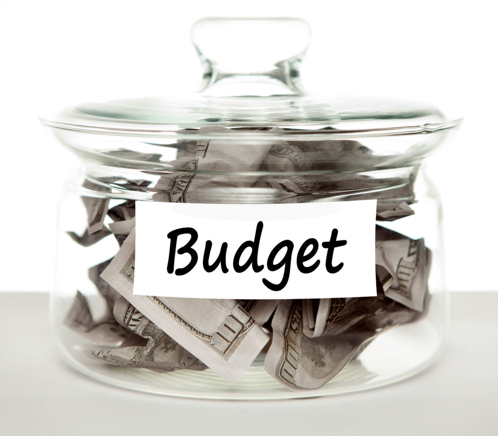A money jar full of American dollars with the word budget written across a label, to emphasis the need to budget even for affordable travel