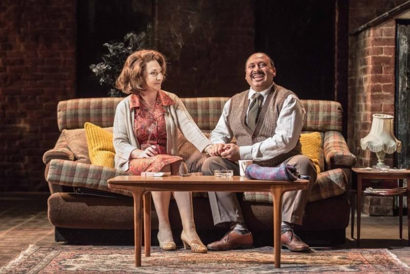 Actors Simon Nagra and Pauline McLynn sitting on a sofa on stage