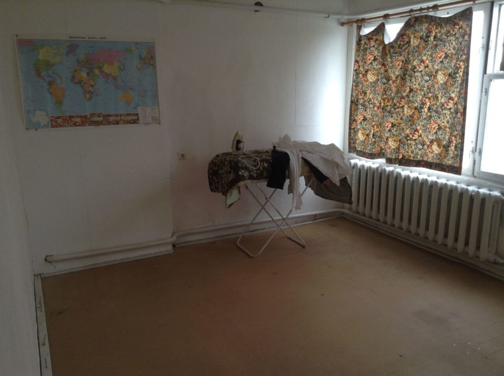 home almost entirely empty with lone ironing board as living room furniture housesitting