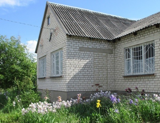 House in rural Ukraine with flowers in an overgrown garden