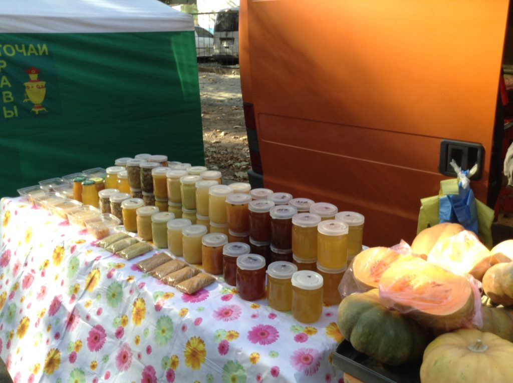 Market Stall with flowered table cloth displaying jars of honey and spice