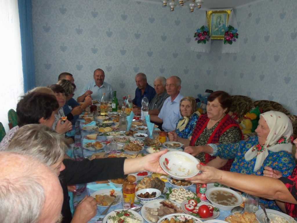 Ukranian feast with neighbours gathered around a table heaving with food