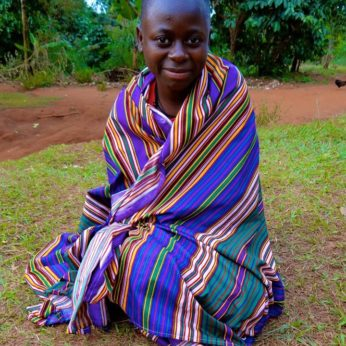 Ugandan girl seated on the ground, in a striking blue wrap