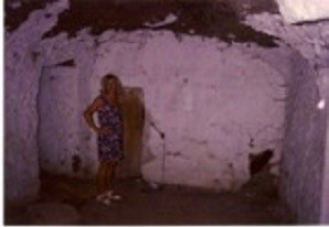 Anne the author standing in the undeveloped living room spade in hand