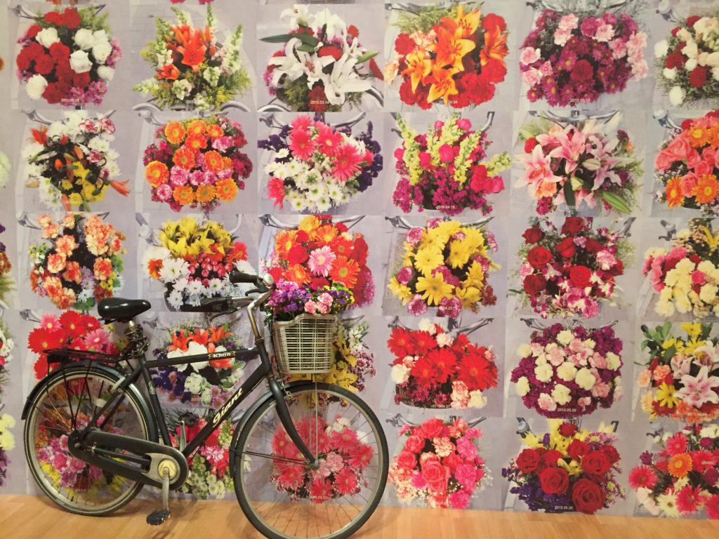 Mural by Ai Wei Wei of all the flowers he placed in the basket of a bicycle for the secret police