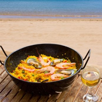 A pan of Spanish Paella at the beach with a glass of white wine