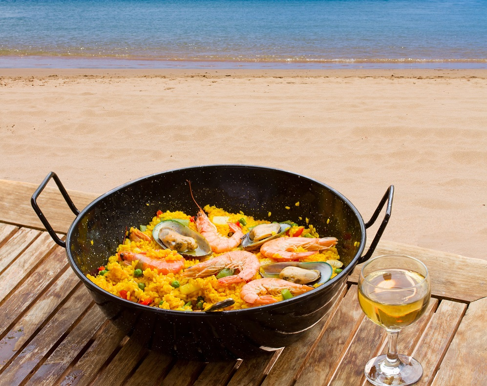 Retired professionals enjoy a pan of Spanish Paella at the beach with a glass of white wine