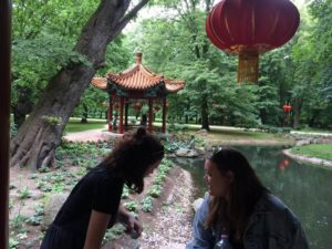 Two girls in the foreground of a picture of a red chinese summer house