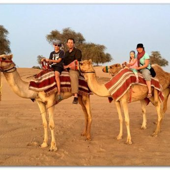 Housesitting family riding two camels in Dubai