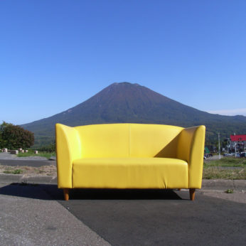 a yellow couch in front of a mountain