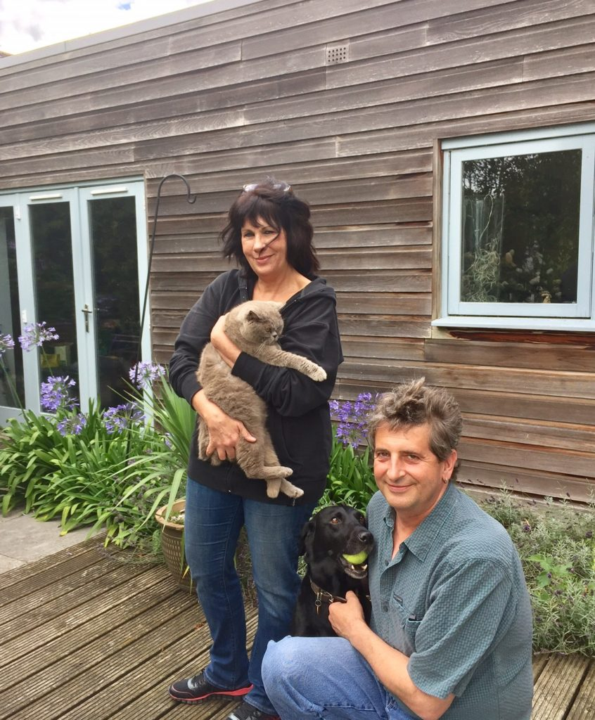 Housesitters pose with their first petsitting charges Hudson the dog and K2 the cat